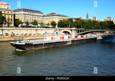 Lastkahn vorbei über die Seine, an den Ufern Menschen den Sommer in Paris verbringen. - Stockfoto