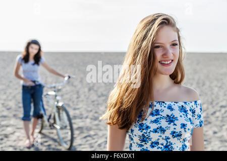Zwei Mädchen stehen auf einem Strand mit Fahrrad; Toronto, Ontario, Kanada - Stockfoto