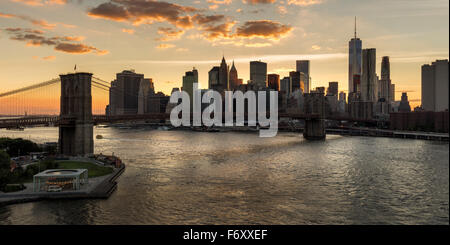 Lower Manhattan Wolkenkratzer und Financial District Skyline bei Sonnenuntergang mit der Brooklyn Bridge über den East River, New York CIty Stockfoto