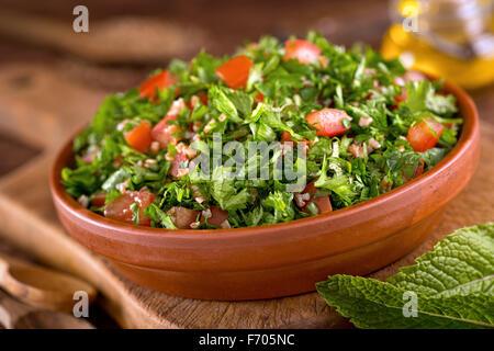 Eine Schüssel mit leckeren frischen Teaneck mit Petersilie, Minze, Tomaten, Zwiebel, Olivenöl, Zitronensaft und - Stockfoto
