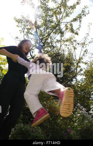 Mutter spielt mit ihrer kleinen Tochter und schwingen sie herum, - Stockfoto