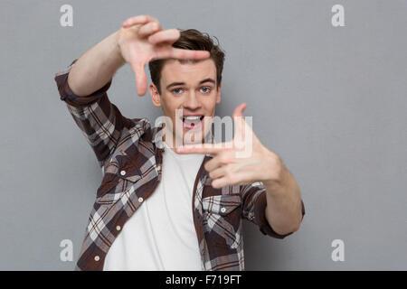 Fröhlich fröhlich Inhalt begeistert hübschen jungen Mann im karierten Hemd macht Frame mit Finger vor dem Gesicht - Stockfoto