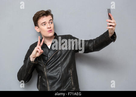 Porträt eines jungen Mannes in Lederjacke, Selfie Foto auf Smartphone über grauen Hintergrund - Stockfoto