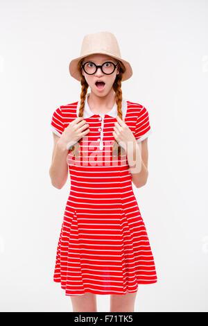 Lustig überrascht Redhead Mädchen mit zwei Zöpfen in Boonie Hut und Runde Brille auf weißem Hintergrund - Stockfoto