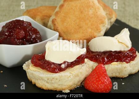 zwei halbiert home gebackene Scones mit Erdbeer-Marmelade und Sahne - Stockfoto
