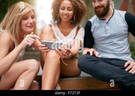 Schuss von jungen Erwachsenen, die auf der Suche etwas Interessantes auf Handy hautnah. Junge Freunde mit Handy sitzen gruppenweise