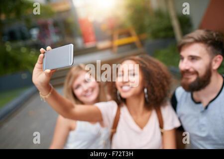 Im Freien Schuss der jungen Frau, die die Selbstporträt auf Handy mit ihren Freunden. Drei junge Freunde nehmen - Stockfoto