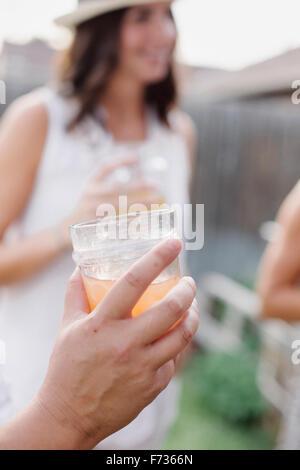 Nahaufnahme von einer Hand hält einen Drink, eine Frau im Hintergrund. - Stockfoto