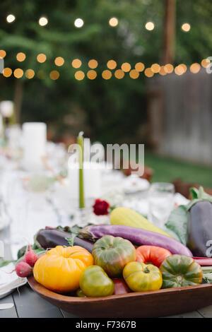 Langer Tisch set mit Teller und Gläser, Essen und trinken in einen Garten, eine Schüssel mit Gemüse im Vordergrund. - Stockfoto
