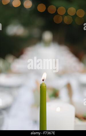 Eine brennende Kerze auf einem Tisch set mit Teller und Gläser, Essen und trinken in einem Garten. - Stockfoto