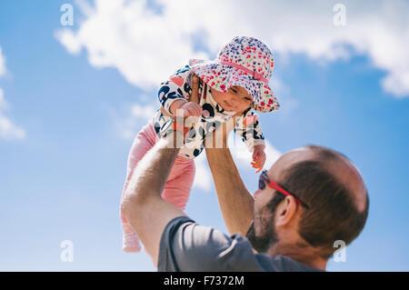 Ein Baby liegend auf einem Schaffell-Teppich, ihre Beine zu treten. - Stockfoto
