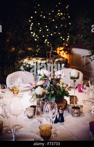 Ein Tisch Gedeckt Für Einen Besonderen Anlass, Mit Einem Floralen Herzstück  Und Kerzen, In