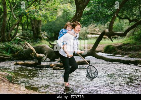 Eine Frau net geben ein Junge eine Huckepack und halten ein Shrimp in einem seichten Bach waten. - Stockfoto