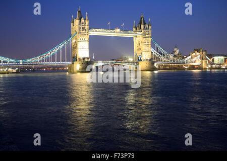 Nachtaufnahme der historischen Tower Bridge in den ruhigen Fluss Themse, London, England - Stockfoto