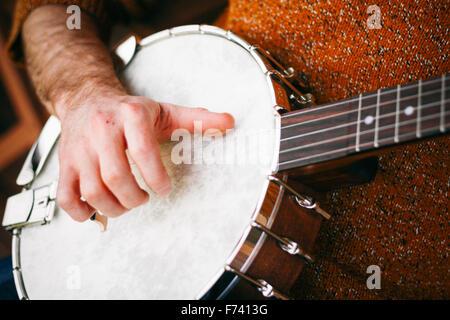 Nahaufnahme eines männlichen Banjo-Spieler auf der Veranda entspannen üben und Kommissionierung entfernt - Stockfoto