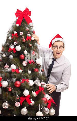 Vertikale Schuss von einem fröhlichen Kerl mit Weihnachtsmütze neben einem Weihnachtsbaum steht und schaut in die - Stockfoto