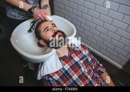Friseur, Haarwäsche von jungen attraktiven Mann mit Bart im karierten Hemd im Friseursalon - Stockfoto
