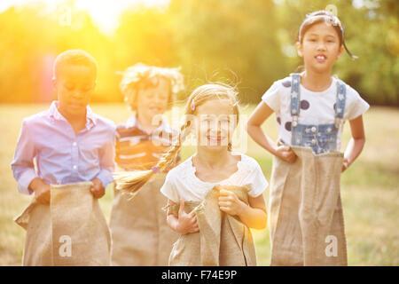 Gruppe von Kindern am Sackhüpfen Lächeln und Spaß - Stockfoto