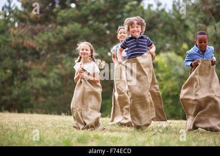 Interracial Gruppe von Kindern mit Fut bei Sackhüpfen - Stockfoto
