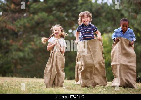 Kinder im Wettbewerb bei Sackhüpfen und Spaß - Stockfoto