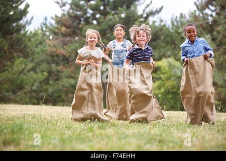 Kinder, die Spaß am Sackhüpfen im park - Stockfoto