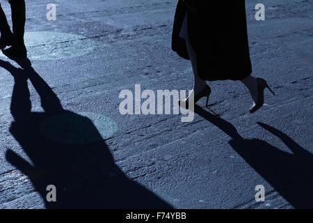 Blaue Nacht Schatten und Silhouetten von unkenntlich Mann und Frau auf einer Stadtstraße - Stockfoto