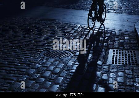 Silhouette eines unkenntlich Mann Radfahren in blaue Nacht Schatten auf einer Straße mit Kopfsteinpflaster - Stockfoto