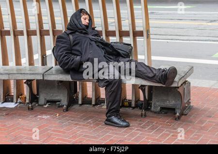 Eine erschöpfte junge Hipster-Frau in alle schwarz gekleidet und trägt Piercings in Nase und Lippen ruht auf einer - Stockfoto