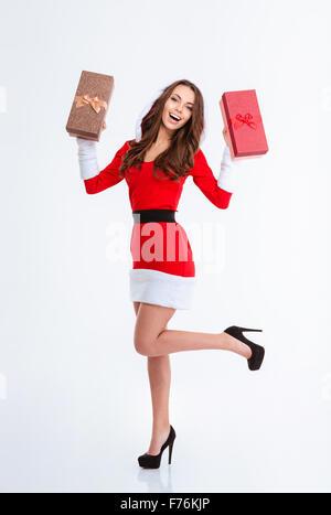 In voller Länge Portrait von eine stets gut gelaunte Frau in Santa Claus Tuch hält Geschenkboxen isoliert auf weißem - Stockfoto