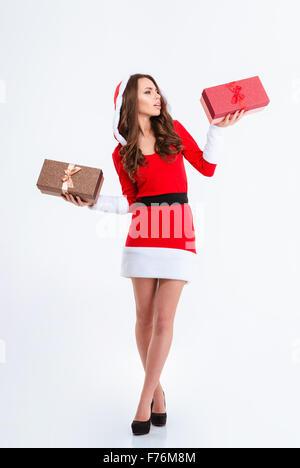 In voller Länge Portrait einer nachdenklichen Frau in Santa Claus Tuch hält zwei Geschenkboxen isoliert auf weißem - Stockfoto