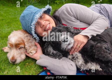 Asiatische Frau mit zwei Cocker Spaniel Hunde Crathes Castle in Aberdeenshire, Schottland. - Stockfoto