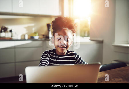 Niedliche junge schwarze Mädchen spielen auf einem Laptop Computer Lächeln glücklich, wie sie im Internet surft, - Stockfoto