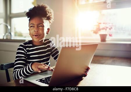 Lustiges kleine schwarze Mädchen mit ihr krauses Afro-Haar oben auf dem Kopf sitzen an einem Tisch zu Hause arbeitet - Stockfoto