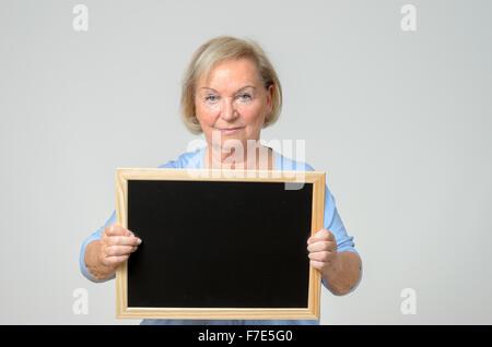 Ernsthafte Seniorin mit einer leeren Tafel oder Schiefer, die sie vor ihrer Brust, Exemplar für Ihren Text hält - Stockfoto
