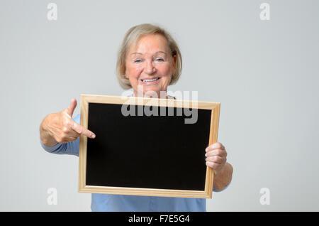 Begeisterte ältere Frau, die auf eine leere Tafel oder Schiefer, die sie vor ihrer Brust mit einem strahlenden Smil - Stockfoto