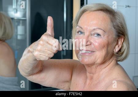 Attraktive blonde senior Frau stehen beim geben eines Daumens Geste, eingewickelt in ein Handtuch im Badezimmer - Stockfoto
