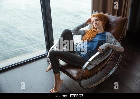 Bildnis einer junge rothaarige Frau entspannend auf Schaukelstuhl mit Meerblick aus dem Fenster - Stockfoto