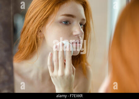 Porträt einer jungen Redhair Frau mit Watte, Blick auf ihr Spiegelbild im Spiegel - Stockfoto
