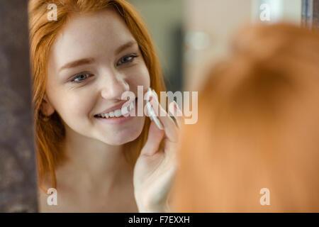 Porträt einer lächelnden Redhair Frau mit Watte, Blick auf ihr Spiegelbild im Spiegel - Stockfoto