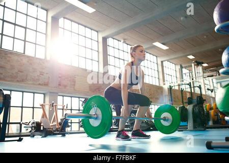 Junge Frau arbeitet hart in der Turnhalle. Passen Sie Sportlerin im Fitnessstudio Gewichte zu heben. - Stockfoto