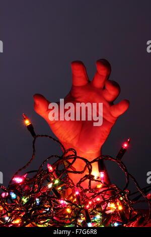 Ein Mann bereitet gegen eine Reihe von Wirren Weihnachten Lichterketten - häusliche Umgebung, England - Stockfoto
