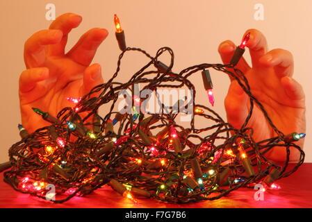 Ein Mann bereitet, sich mit einem Haufen von Wirren Weihnachts-Lichterketten in häuslicher Umgebung, England UK - Stockfoto