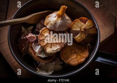 Gebratener Knoblauch Zwiebeln halbieren in einer Pfanne. - Stockfoto