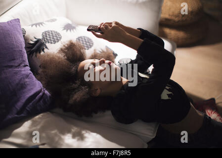 Mädchen liegend gegen Sofa, vertieft in smartphone - Stockfoto