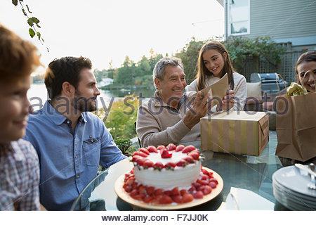 Senior woman Geburtstag Geschenke Familie am See Terrasse öffnen - Stockfoto