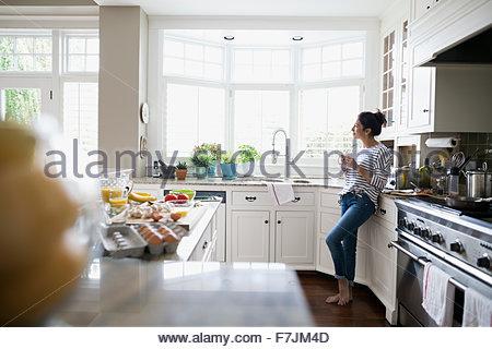 Nachdenkliche Frau trinkt Kaffee Blick Fenster Küche - Stockfoto