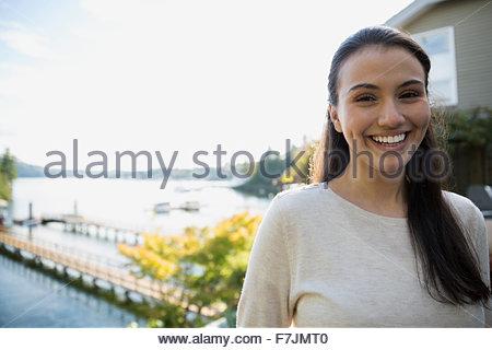Porträt lächelnde junge Frau auf See-Terrasse - Stockfoto