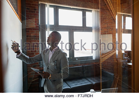 Geschäftsmann am Whiteboard im Büro schreiben - Stockfoto