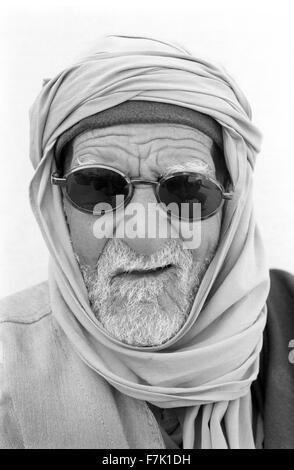 Eine Nahaufnahme Portrait eines älteren tunesischen Mann mit Sonnenbrille. Tozeur, Tunesien, Nord-Afrika. - Stockfoto