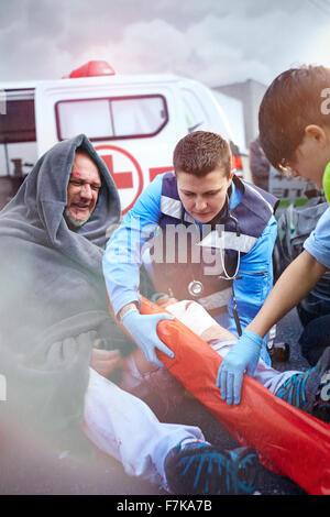 Rettungskräfte Vorbereitung Vakuum Bein Schiene auf Auto Unfallopfer im Straßenverkehr - Stockfoto